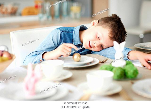 Boy at dining table playing with golden easter egg on plate