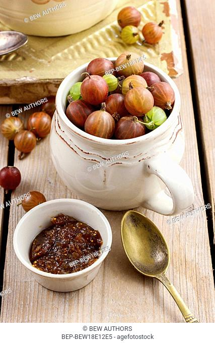 Jug of gooseberry fruits and bowl of gooseberry jam on wooden table