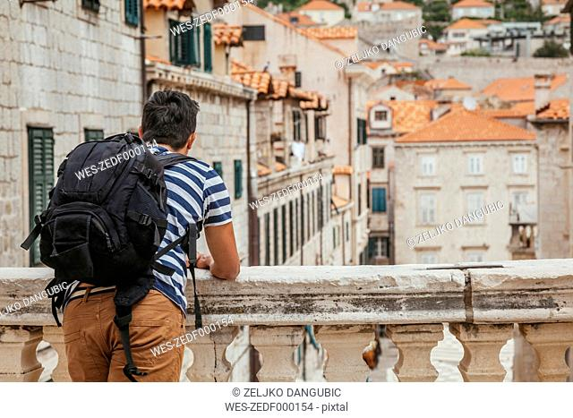 Croatia, Dubrovnik, back view of tourist with backpack looking at the city