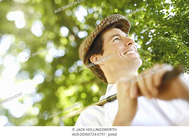Low angle view of a mid adult man holding a golf club and smiling