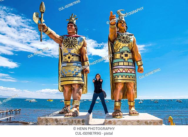 Woman posing between statues of Sun God and Moon Goddess at Lake Titicaca, Bolivia