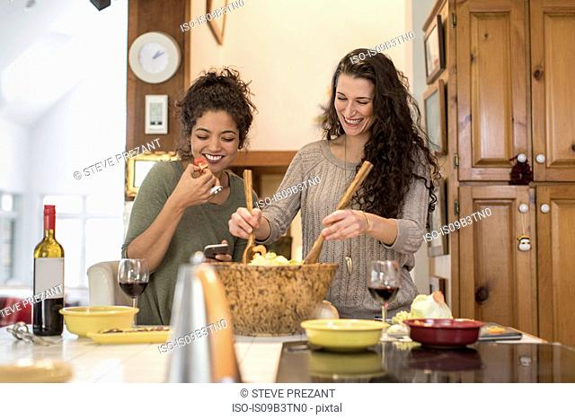 Two female friends preparing and eating salad at kitchen counter