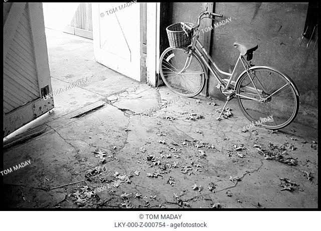 Old fashioned bike parked near barn door