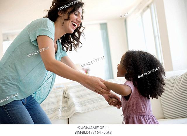 Mother and daughter playing in living room