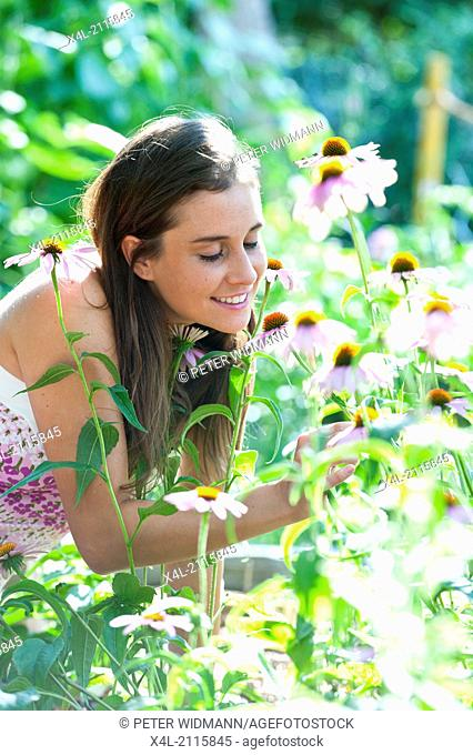 Young, beautiful woman in garden, Echinacea purpurea (model-released)