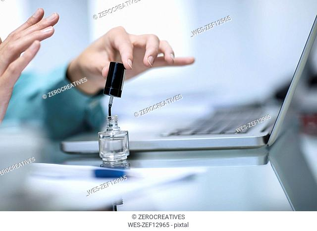 Woman varnishing her finger nails in office