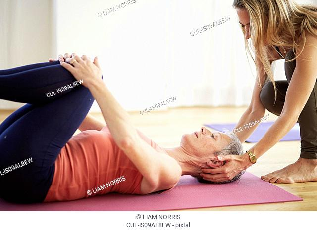 Mature female student lying on back holding knees in pilates class