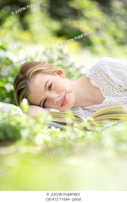 Woman relaxing in grass with book