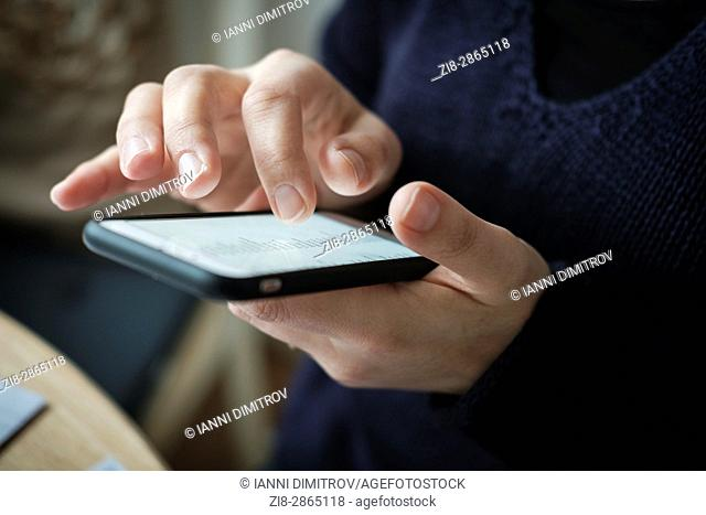 Close-up of woman using touch screen mobile phone