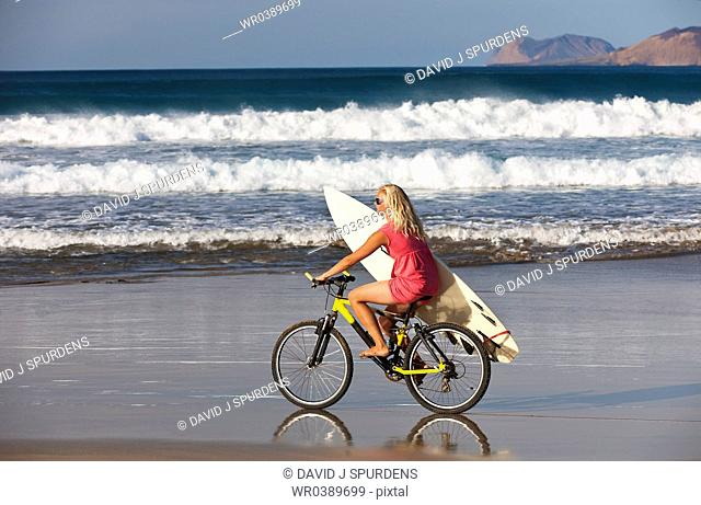 Surfer girl rides to the Ocean waves on mountain bike