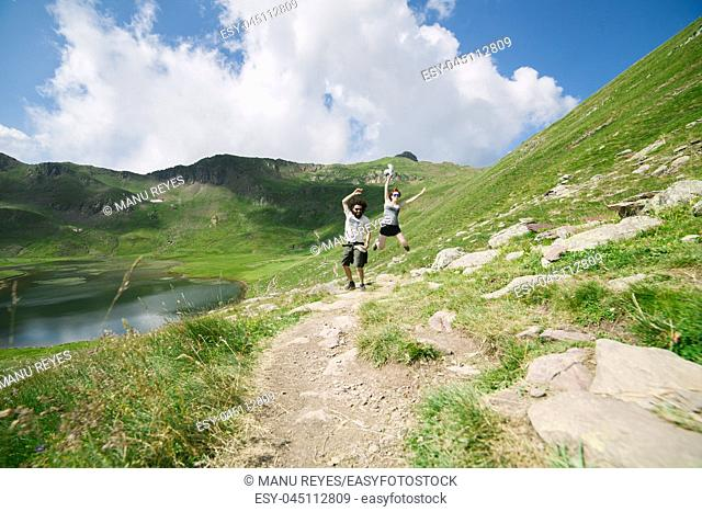 Young couple jumping in a big valley with glacial lake on background, in Ordesa, Huesca, concept of freedom