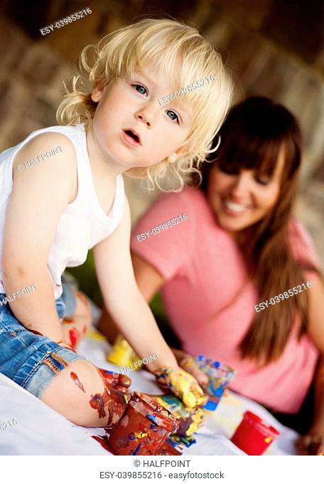 Cute child painting with vibrant colors in the garden