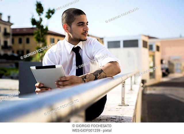 Young businessman with tablet looking at distance