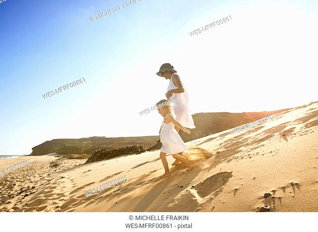 Spain, Fuerteventura, mother running with daughter on the beach