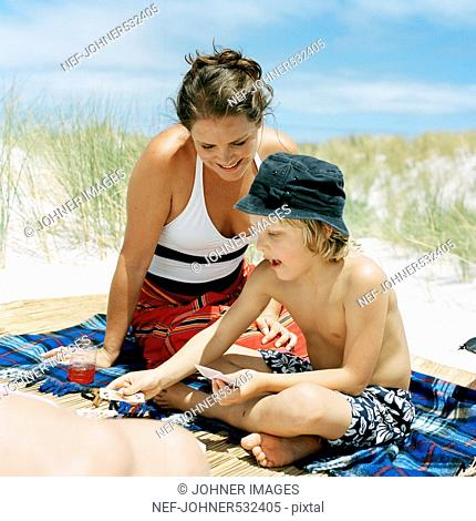 Mother and son playing cards on the beach, Sweden
