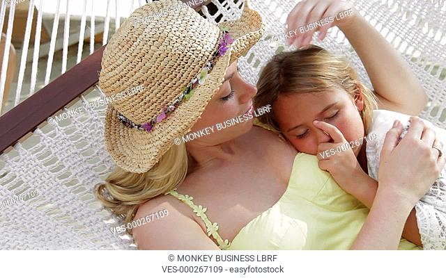 Mother cuddling daughter as they swing gently in hammock.Shot on Canon 5d Mk2 with a frame rate of 30fps