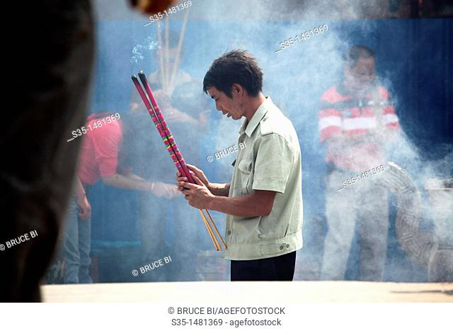 A Prayer offer incense to Buddha in Yuantong Temple the famous Buddhist temple build during Tang Dynasty  Kunming  China