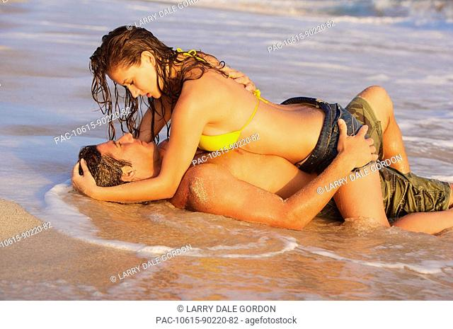 Hawaii, Oahu, Sexy couple share a romantic moment at the beach