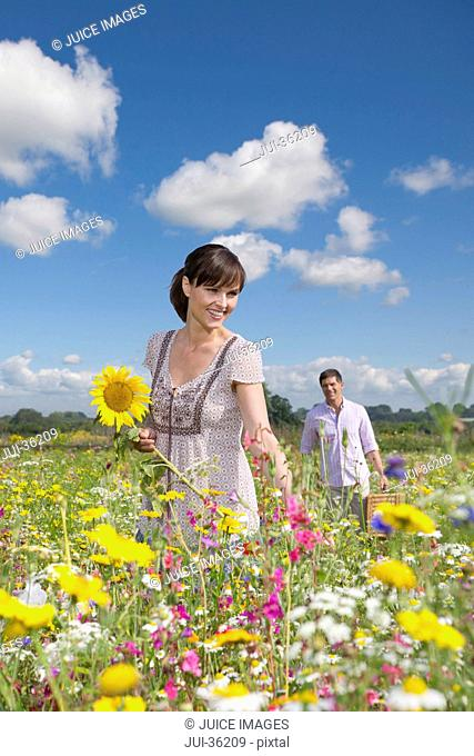 Smiling couple among wildflowers in sunny meadow