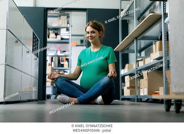 Smiling pregnant woman sitting on floor in office having a yoga break