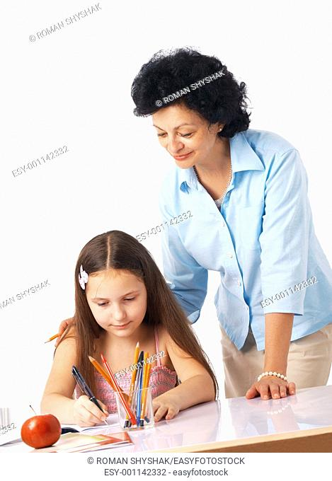 Grandmother standing over her granddaughter and helping her with home-work