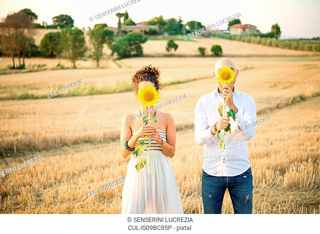 Heterosexual couple in field, holding sunflowers in front of faces