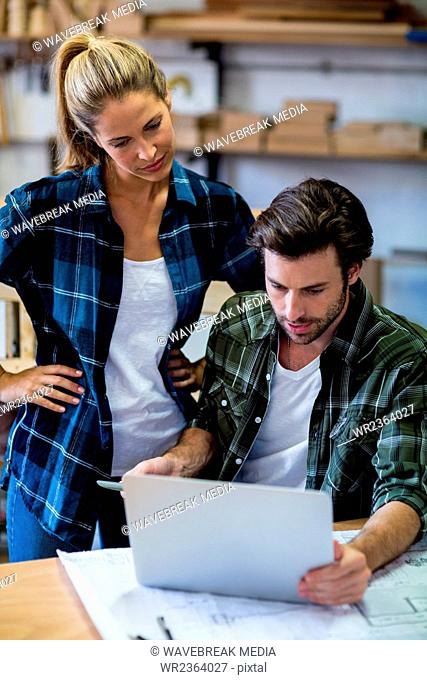 Male and female carpenters using laptop