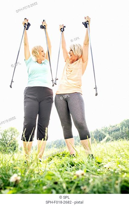 MODEL RELEASED. Two women with walking poles raised in air
