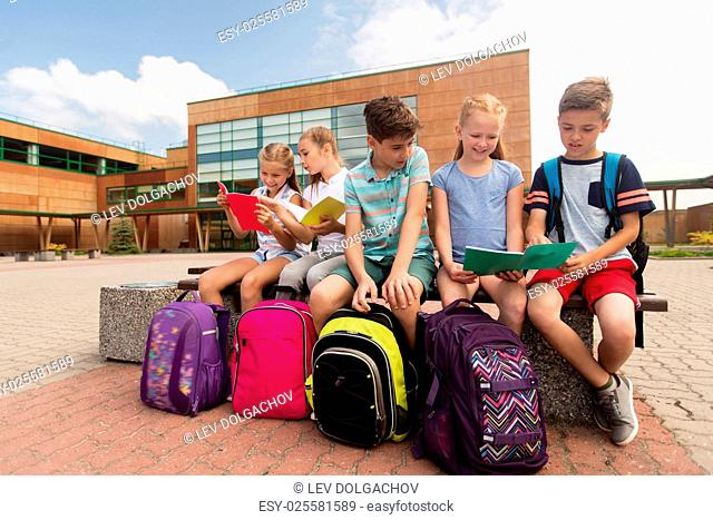 primary education, friendship, childhood, communication and people concept - group of happy elementary school students with backpacks and notebooks sitting on...