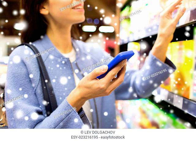 sale, shopping, consumerism and people concept - happy young woman with smartphone choosing and buying food in market over snow effect