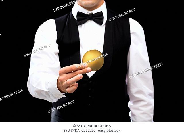 close up of casino dealer holding golden coin
