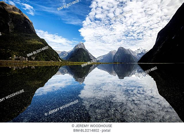Mountains reflecting in remote lake, Milford Sound, Fiordland, New Zealand