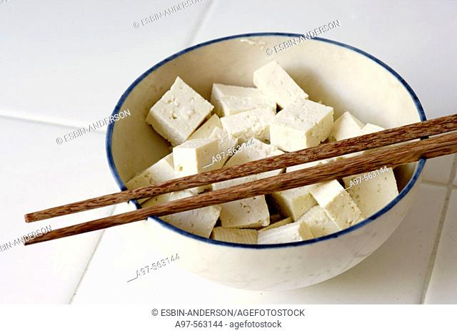 Pieces of Tofu cut into cubes and sitting in a bowl with a pair of chopsticks resting on top