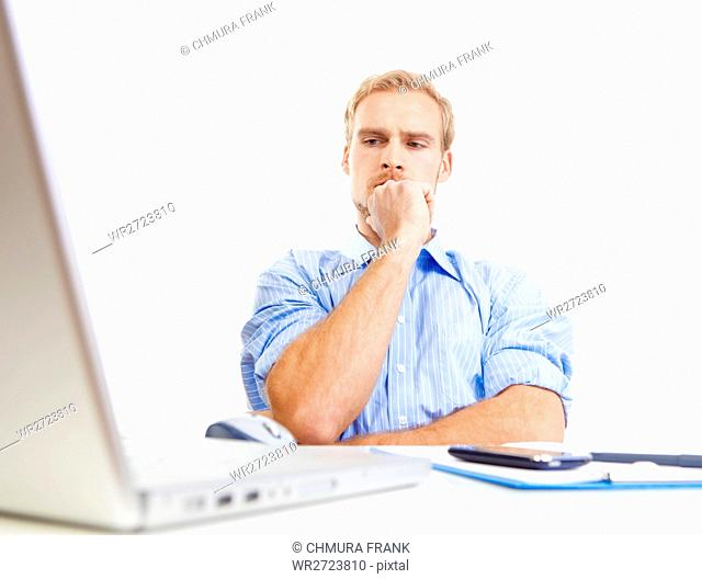 young man at desk in office thinking, contemplating