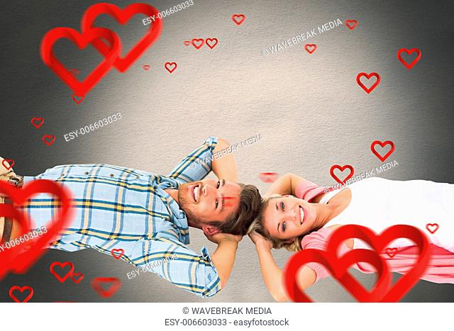 Composite image of attractive young couple lying smiling at camera
