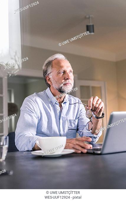 Portrait of pensive mature man sitting at table with laptop looking at distance
