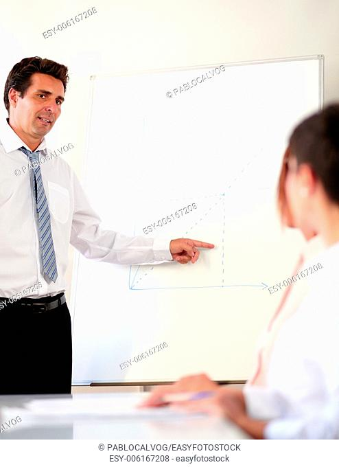 Portrait of a mature businessman working on his presentation while standing in front of white board