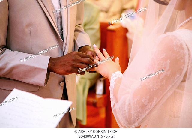 Cropped view of bridegroom putting ring on brides finger at wedding ceremony