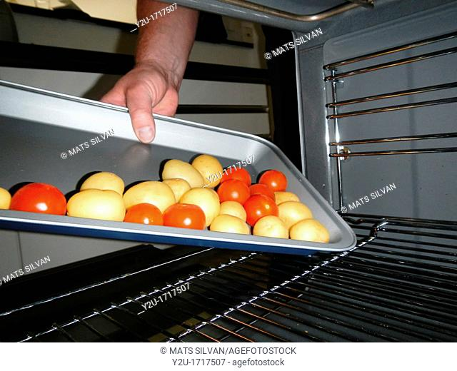 View from inside an oven with potatoes and tomatoes and a red paprika