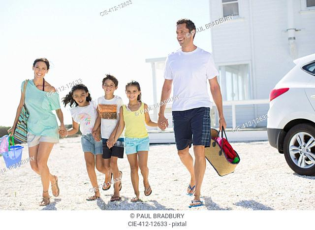 Family holding hands and walking with beach gear in sunny driveway