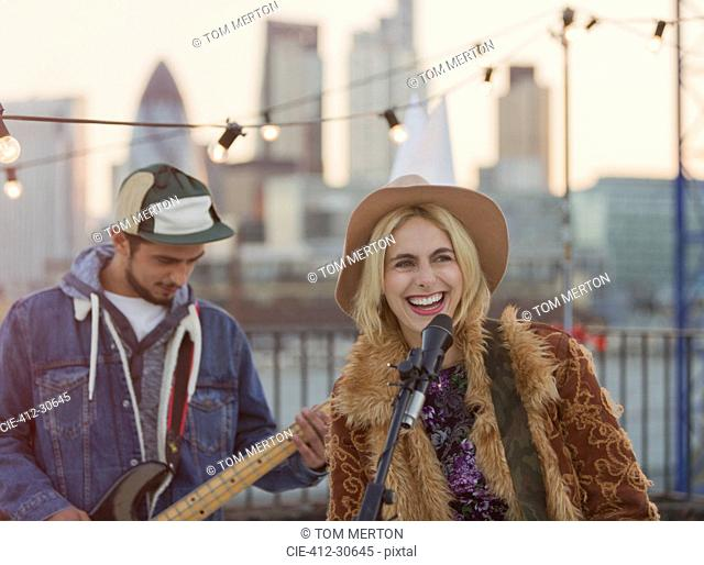 Musicians playing guitar and singing at rooftop party
