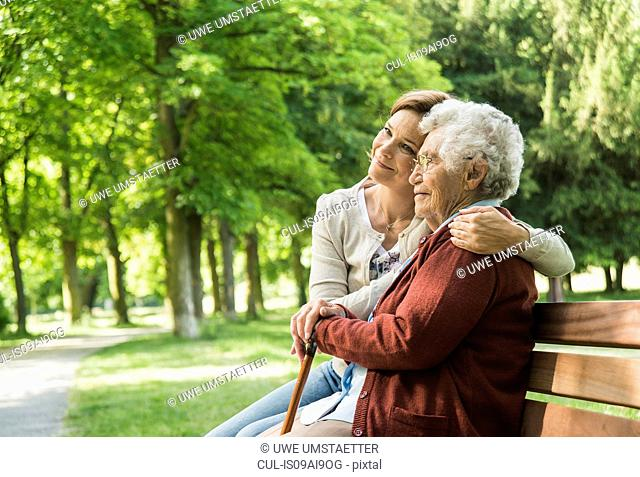 Senior woman sitting on park bench with granddaughter