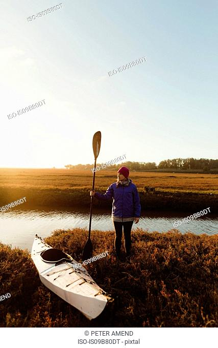 Woman kayaker on riverbank at sunset, Morro Bay, California, USA