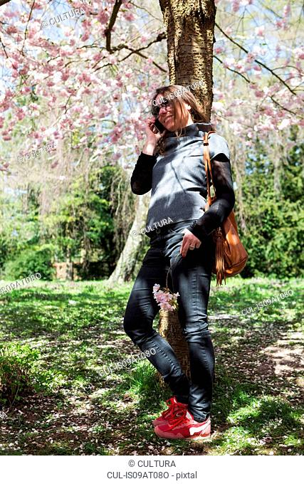 Mature woman chatting on smartphone whilst leaning against park tree