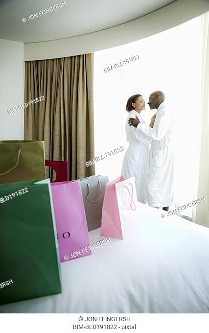 Couple kissing in bathrobes with shopping bags on bed