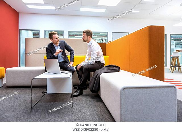 Businessmen sitting in conversation pit, discussing in front of laptop