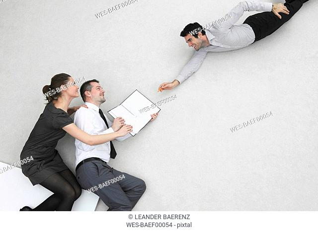 Three business people, businessman signing contract, elevated view