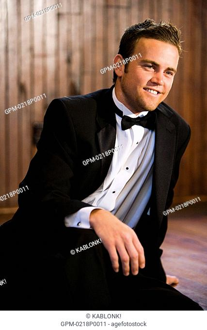 Young groom in tuxedo sitting at altar of church
