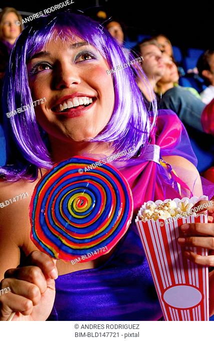 Woman eating candy and popcorn in movie theater