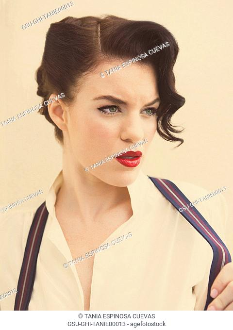 Portrait of Intense Young Adult Woman Tugging on Suspenders
